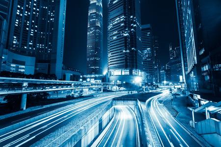 Futuristische nachtcityscape weergave met verlichte wolkenkrabbers en stadsverkeer over straat. Hongkong