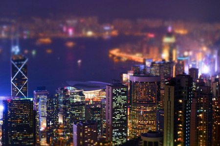 Night aerial view panorama of Hong Kong skyline and Victoria Harbor. Tilt shift effect. Abstract futuristic cityscape with modern skyscrapers