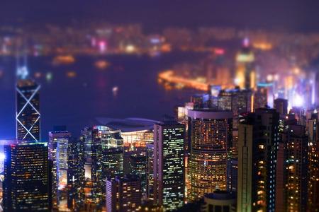 Hong Kong のスカイラインとビクトリア ・ ハーバーの夜景を空撮。シフト効果を傾けます。近代的な高層ビルと抽象的な未来的な都市の景観