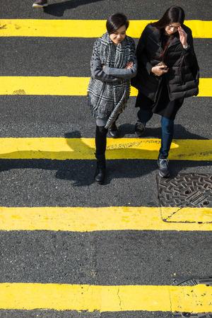 zebra crossing: HONG KONG - JAN 17, 2015: Pedestrians people moving on zebra crosswalk at crowded city. Hong Kong