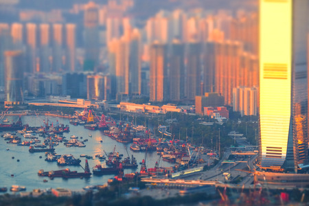 tilt: Tilt shift aerial view panorama of Hong Kong skyline and Victoria Harbor at sunset. Travel destinations Stock Photo