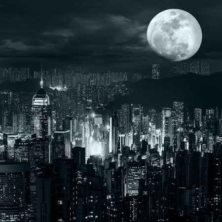 劇的な曇り空の下で満月の夜に Hong Kong スカイラインの夜景空撮