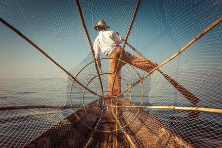 un p�cheur: P�cheur birman sur le bateau de bambou capture de poissons de fa�on traditionnelle avec la main net. Lac Inle, Myanmar (Birmanie) destination Voyage Banque d'images