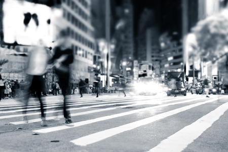 Blurred image of people moving in crowded night city street. Art toning abstract urban background. Hong Kong Archivio Fotografico