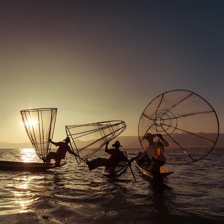 pecheur: P�cheur birman sur le bateau de bambou capture de poissons de fa�on traditionnelle avec la main net. Lac Inle, Myanmar (Birmanie) destination Voyage Banque d'images