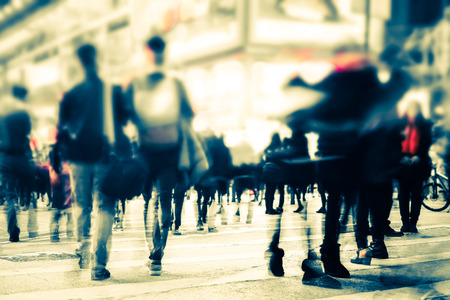 Blurred image of people moving in crowded night city street. Art toning abstract urban background. Hong Kong Imagens