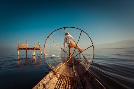 Burmese fisherman on bamboo boat catching fish in traditional way with handmade net. Inle lake, Myanmar (Burma) travel  destination