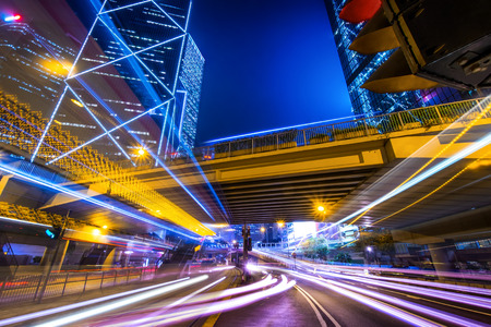 Futuristic night cityscape view with illuminated skyscrapers and city traffic across street. Hong Kong
