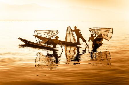 pescador: Pescadores birmanos en el barco de bamb� captura de peces en forma tradicional con red hecha a mano. Lago Inle, Myanmar (Birmania) destino de viaje Foto de archivo