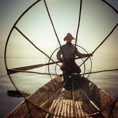 destinations: Burmese fisherman on bamboo boat catching fish in traditional way with handmade net. Inle lake, Myanmar (Burma) travel  destination