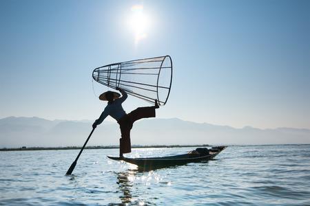 pescador: Pescadores birmanos en el barco de bambú captura de peces en forma tradicional con red hecha a mano. Lago Inle, Myanmar (Birmania) destino de viaje Foto de archivo