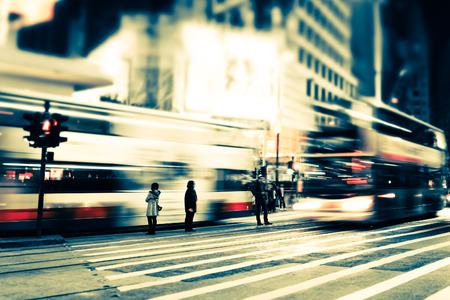 Abstract cityscape blurred background, art toning. Night view of modern city street with moving transport, illuminated skyscrapers and walking people. Hong Kong