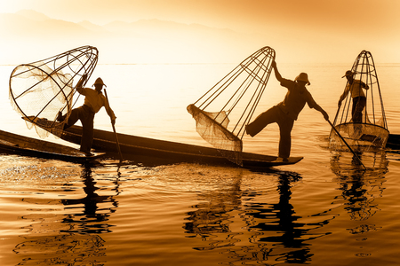 Burmese fisherman on bamboo boat catching fish in traditional way with handmade net. Inle lake, Myanmar Burma travel  destination