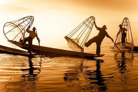 pescador: Pescadores birmanos en el barco de bambú captura de peces en forma tradicional con red hecha a mano. Lago Inle, destino de viaje Myanmar Birmania
