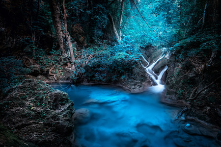 Mystery night at deep tropical rain forest with flowing cascade waterfall. Fantasy jangle landscape.  Erawan, National Park Kanchanaburi, Thailand