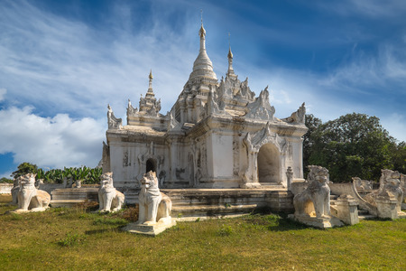 tourist attraction: White Pagoda at Inwa ancient city with lions guardian statues. Amazing architecture of old Buddhist Temples. Myanmar Burma travel landscapes and destinations
