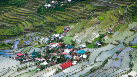 paddy fields: Village houses near rice terraces fields. Amazing abstract texture with sky colorful reflection in water. Ifugao province. Banaue, Philippines UNESCO heritage Stock Photo