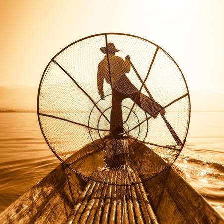 destinations: Burmese fisherman on bamboo boat catching fish in traditional way with handmade net. Inle lake, Myanmar Burma travel  destination