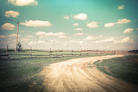 Sunny day in countryside. Summer landscape with rural road, wooden fence and electric poles under blue cloudy sky. Nature background in vintage style Stock Photo