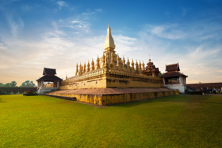 religious building: Religious architecture and landmarks. Golden buddhist pagoda of Phra That Luang Temple under sunset sky. Vientiane, Laos travel landscape and destinations