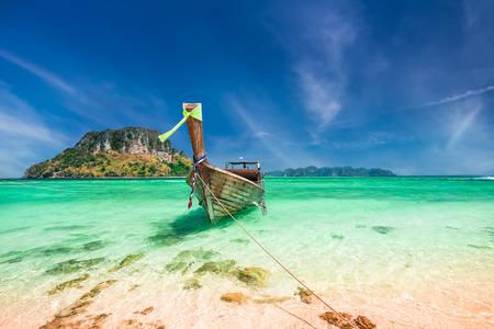 ao: Thai traditional wooden boat with ribbon decoration at ocean shore near Koh Tup island. Thailand, Krabi province, Ao Nang Stock Photo
