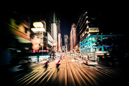 Bewegen door moderne stad straat met verlichte wolkenkrabbers. Hong Kong. Abstracte stadsgezicht verkeer achtergrond met silhouetten van mensen bij zebra kruispunt. Motion blur, art toning Stockfoto