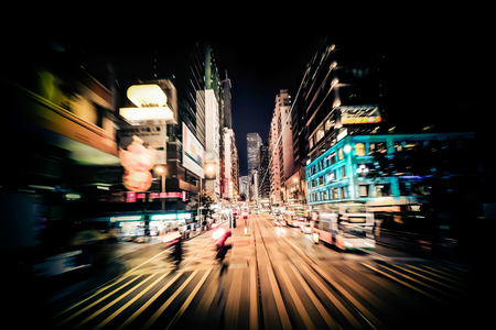 Światła: Poruszanie się nowoczesnego miasta ulicy z oświetlonych wieżowców. Hongkong. Streszczenie miasta tle ruchu z ludźmi sylwetki zebra na skrzyżowaniu. Poruszenie, sztuka tonujące