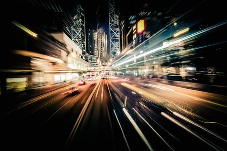 Fondo abstracto del tráfico urbano con el desenfoque de movimiento, el arte de tonificación. Moviéndose a través de moderna calle de la ciudad con rascacielos iluminados. Hong Kong
