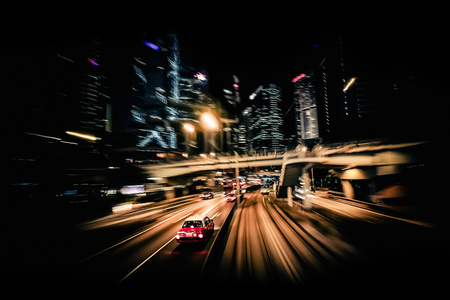 night view: Moving through modern city street with illuminated skyscrapers. Hong Kong. Abstract cityscape traffic background with taxi car driving at night. Motion blur, art toning Stock Photo