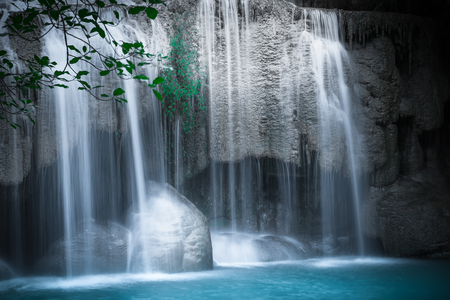 waterfall in the forest: Jangle landscape with flowing turquoise water of Erawan cascade waterfall at deep tropical rain forest. National Park Kanchanaburi, Thailand