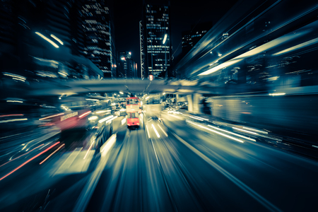 Abstract cityscape traffic background with motion blur, art toning. Moving through modern city street with  illuminated skyscrapers. Hong Kong