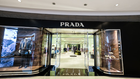 window display: HONG KONG - 23 JAN, 2015: Prada boutique display window with luxury clothes and accessories. Italian luxury fashion house produces shoes, luggage, perfumes, watches.  Ffounded in 1913 by Mario Prada