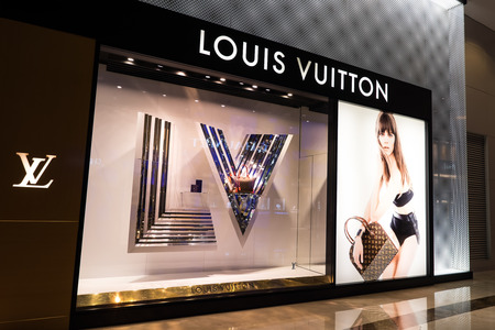 louis vuitton: HONG KONG - 22 JAN, 2015: Louis Vuitton boutique display window with mannequin in luxury clothes and accessories for exclusive shopping. French fashion house founded in 1854 by Louis Vuitton Editorial