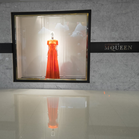 haute couture: HONG KONG - 23 JAN, 2015: Alexander Mcqueen fashion boutique display window with mannequin dressed in haute couture luxury red female dress