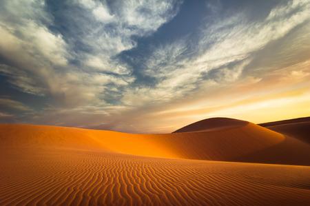 anochecer: concepto de calentamiento global. dunas de arena solo bajo el cielo de la tarde dramática puesta de sol en la sequía paisaje del desierto