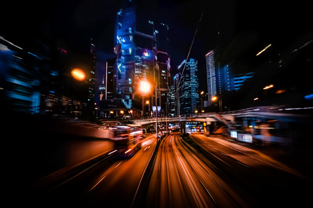 Moving through modern city street with illuminated skyscrapers. Hong Kong.