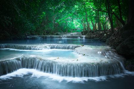 paisagem: Jangle paisagem fluindo com água azul-turquesa de Erawan cachoeira cascata em profunda floresta tropical. Parque Nacional de Kanchanaburi, Tailândia