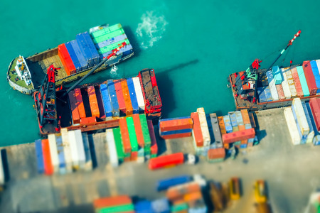 terminals: Tilt shift blur effect. Aerial view cargo ships loaded by crane with cargo containers at a busy port terminal. Hong Kong