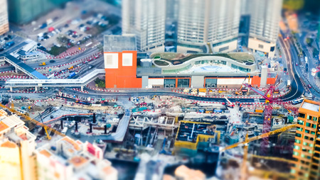 tilt shift: Tilt shift blur effect. Amazing aerial cityscape view with crane working at building construction. Hong Kong. Abstract futuristic cityscape with modern skyscrapers