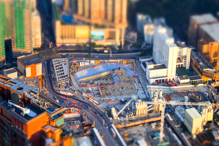 office building: Tilt shift blur effect. Amazing aerial cityscape view with crane working at building construction. Hong Kong. Abstract futuristic cityscape with modern skyscrapers