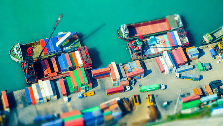 tilt: Tilt shift blur effect. Aerial view cargo ships loaded by crane with cargo containers at a busy port terminal. Hong Kong