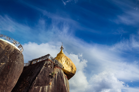 trave: Golden Rock with row of traditional wind bells under blue sky. Most sacred Buddhist place with rock balancing on three hairs of Buddha. Kyaiktiyo, Myanmar (Burma) trave