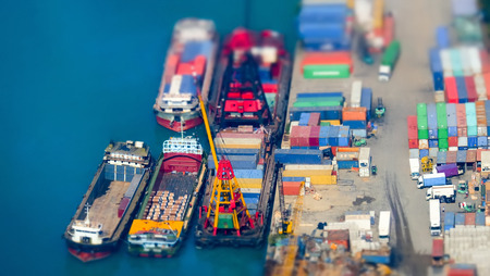 Tilt shift blur effect. Aerial view cargo ships loaded by crane with cargo containers at a busy port terminal. Hong Kong