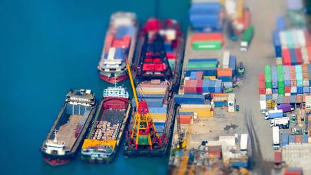 szállítás: Tilt Shift elmosódás. Légifelvételek teherhajók által betöltött daru a konténer egy forgalmas kikötői terminál. Hong Kong Stock fotó