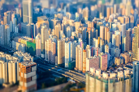developing: Abstract futuristic cityscape with modern skyscrapers. Hong Kong aerial view evening panorama. Tilt shift effect