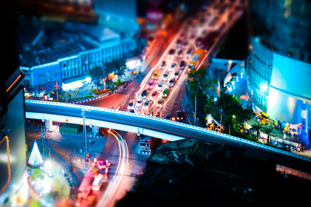 blur effect: Tilt shift blur effect. Futuristic night cityscape aerial view panorama with illuminated skyscrapers and city traffic across streets. Bangkok, Thailand Stock Photo