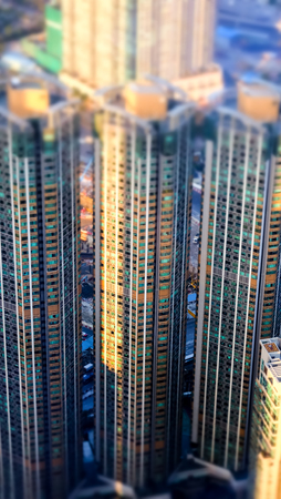 tilt view: Abstract futuristic cityscape with modern skyscrapers. Hong Kong aerial view evening panorama. Tilt shift effect
