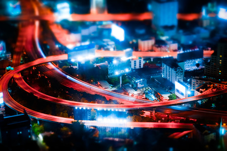 night shift: Tilt shift blur effect. Futuristic night cityscape aerial view panorama with illuminated skyscrapers and city traffic across streets. Bangkok, Thailand Stock Photo