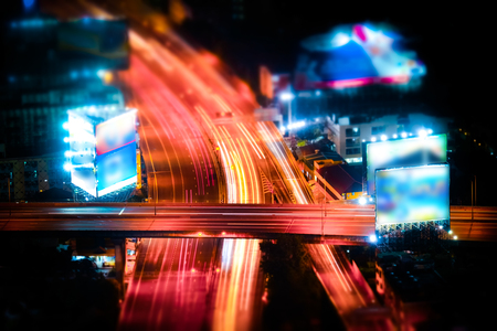 highway interchange: Tilt shift blur effect. Abstract cityscape background. Futuristic night aerial view of highway interchange with moving cars. Bangkok, Thailand