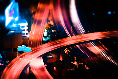night shift: Tilt shift blur effect. Abstract cityscape background. Futuristic night aerial view of highway interchange with moving cars. Bangkok, Thailand
